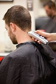 stock photo of clippers  - Portrait of man having a haircut with a hair clippers - JPG