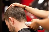 stock photo of hair cutting  - Close up of a male student having a haircut with hair clippers - JPG