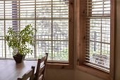 A Wooden Kitchen Table And Chairs Near A Window With A Potted Plant And A Dog Looking In The Side Wi poster