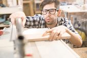 Portrait Of Focused Modern Carpenter Working With Wood In Joinery Shop Blowing Sawdust Off Workstati poster