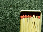 Постер, плакат: A Group Of Wooden Match Sticks With Red Head In Match Box Over Black Or Dark Granite Texture With Co