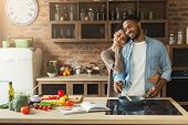 Happy African-american Couple Cooking And Tasting Healthy Food In Their Loft Kitchen At Home. Woman  poster