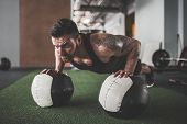 Plank It. Confident Bearded, Tattoed Muscled Man Wearing Sport Wear And Doing Plank Position On Gym  poster