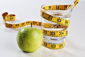image of tape-measure  - Glass of water on a reflective tabletop with an apple and tape measure - JPG