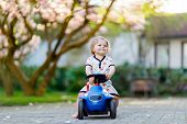 Cute Little Baby Girl Playing With Blue Small Toy Car In Garden Of Home Or Nursery. Adorable Beautif poster