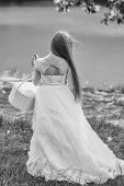 Small Girl Kid With Long Blonde Hair In Prom Princess White Dress Standing Sunny Day Outdoor Near Wa poster