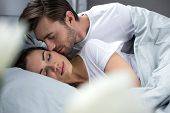 Husband Tenderly Kissing Sleeping Wife In Bed poster