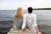 picture of stressless  - Rear view of couple sitting on a wooden bridge by a lake - JPG