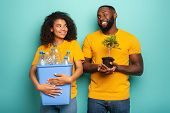 Happy Couple Hold A Plastic Container With Bottles And A Small Tree Over A Light Blue Color. Concept poster