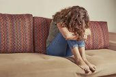 Depressed Woman Sit On Sofa At The Living Room. Lonely Sad Woman Bend Down The Head. Depression And  poster