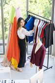 Top view of young adult fashion designer standing near clothing rack with colorful and fashionable s poster