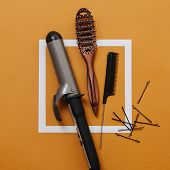 Barber Tools: Curling Iron, Hairbrush, Rat Tail Comb, Bobby Pins Over Orange poster