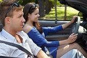 picture of seatbelt  - Young couple sits in cabriolet fastened with seatbelts - JPG