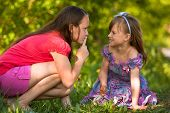 foto of shh  - Young girl with her finger over her mouth shows for mischievous child  - JPG