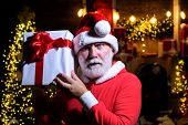 Santa Claus Holds Present. Santa Man With Christmas Gift Box. Merry Christmas And Happy New Year. Ne poster
