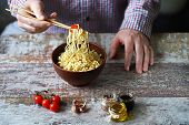 Selective Focus. A Man Holds Chopsticks With Chinese Noodles. Chinese Noodle Bowl With Spices. poster