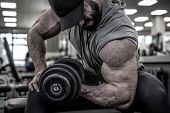 Strong Young Bearded Man In Cap Lifting Heavy Weight Dumbbell On Muscle Biceps Sitting With Great Ef poster