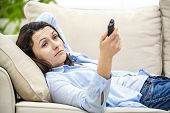 Crop. Bored And Relaxed Woman Is Watching Tv, Laying On A Sofa. Close Up. poster