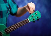 Green Ukulele In The Hands Of A Girl. Tune A Little Guitar. Girl Tunes Ukulele. poster