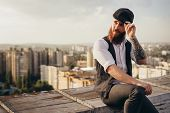 Trendy Bearded Man With Tattooed Arm Adjusting Cap And Looking Away While Sitting On Shabby Border O poster