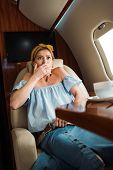 Selective Focus Of Scared Woman With Fear Of Flight Covering Mouth During Flight In Private Plane poster