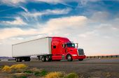 stock photo of delivery-truck  - Red truck moving on a vibrant highway - JPG