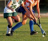 stock photo of battle  - Two women battle for control of ball during field hockey game - JPG