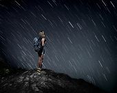 Tourist with backpack standing on top of a mountain and enjoying night sky view with stars