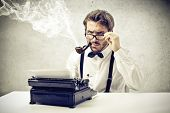 stock photo of nerd  - writer smokes a pipe and writes with typewriter - JPG