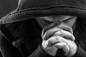 stock photo of hooligan  - Despair bandit praying God for forgiveness - JPG
