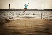 stock photo of dock a pond  - Teen Boy Jumping off a dock - JPG