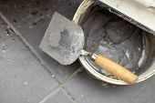 stock photo of trowel  - Renovation at home dirty trowel and bucket with mortar on construction building site - JPG
