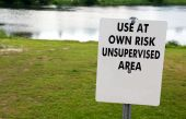 """picture of ares  - """"Use at own risk. Unsupervised ares"""" sign on river shore. - JPG"""