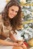 Portrait Of Happy Young Woman With Latte Macchiato Near Christmas Tree