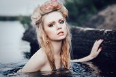 stock photo of pale skin  - Art fashion portrait of young blond girl with flowers in hair in water - JPG