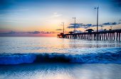 stock photo of outer  - The rising sun peeks through clouds and is reflected in waves by the Nags Head fishing pier on the outer banks of North Carolina - JPG