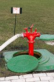 picture of firehose  - Red fire hydrant stands on roadside in manhole - JPG
