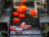 stock photo of workplace safety  - steel gear hot forging in continuous production line - JPG