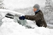 stock photo of cold-weather  - Young man brushing the snow off his car on a cold winter day in snowfall