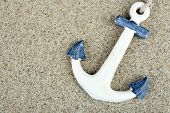 stock photo of anchor  - Anchor on sand background - JPG