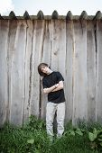 stock photo of oblique  - oblique standing teenage boy in front of a wooden wall - JPG