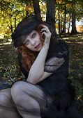 image of black widow spider  - Pretty redhead wearing black dress and black veil in forest - JPG