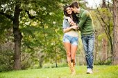 foto of heterosexual couple  - Young cheerful couple attractive brunette and her handsome boyfriend embracing and smiling walking through the park - JPG