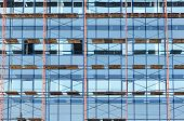 stock photo of scaffold  - Glass office building under construction with scaffolding - JPG