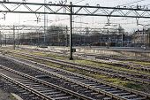 stock photo of railroad yard  - Railway tracks in early morning sun at the Dutch station of The Hague - JPG
