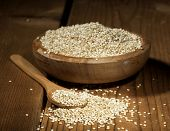 foto of quinoa  - Uncooked quinoa in the wooden bowl and spoon on a wooden background - JPG