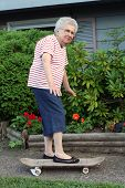 stock photo of unnatural  - Senior citizen woman on a skateboard - JPG