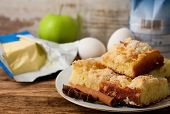 image of cinnamon  - Horizontal photo of Plate with several portions of apple cake and spice anise and cinnamon with butter apple eggs and flour in background placed on old worn wooden board - JPG