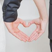 image of married couple  - wedding couple showing shape of heart from their hands - JPG