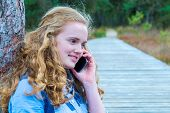 image of natural blonde  - Blonde caucasian teenage girl phoning with mobile telephone along wooden path in nature landscape - JPG